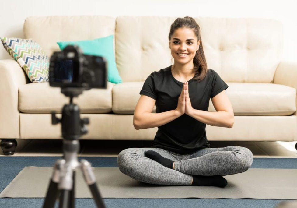 Gorgeous young Hispanic fitness blogger giving some advice on practicing yoga at home on video
